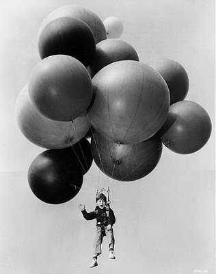 child flying away with balloons
