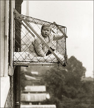 toddler in cageon side of building