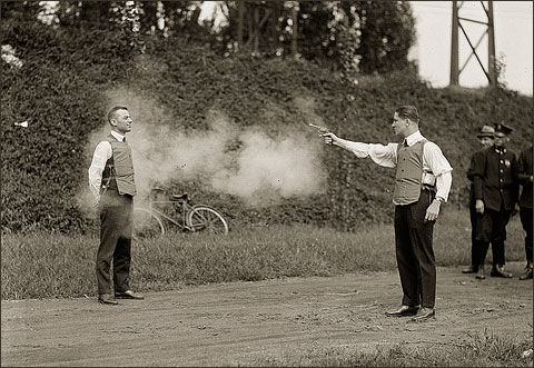vintage photo of man shooting another man wearing a lead vest