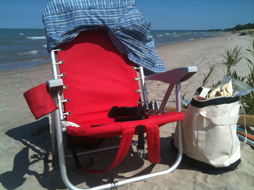 red chair on beach with beach bag next to it