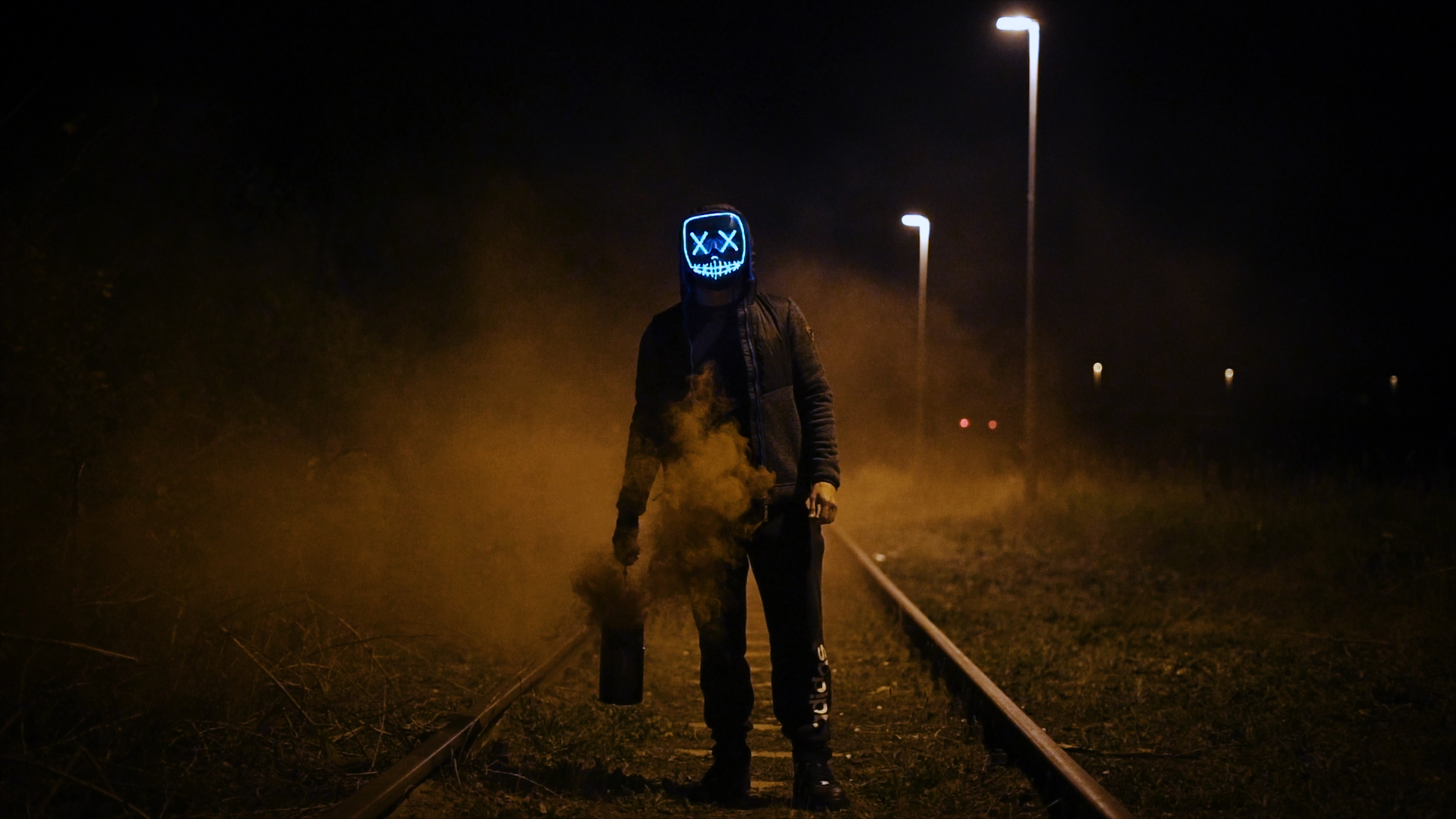 a horseman of the apocalypse -- figure walking through shadows and fog on train tracks