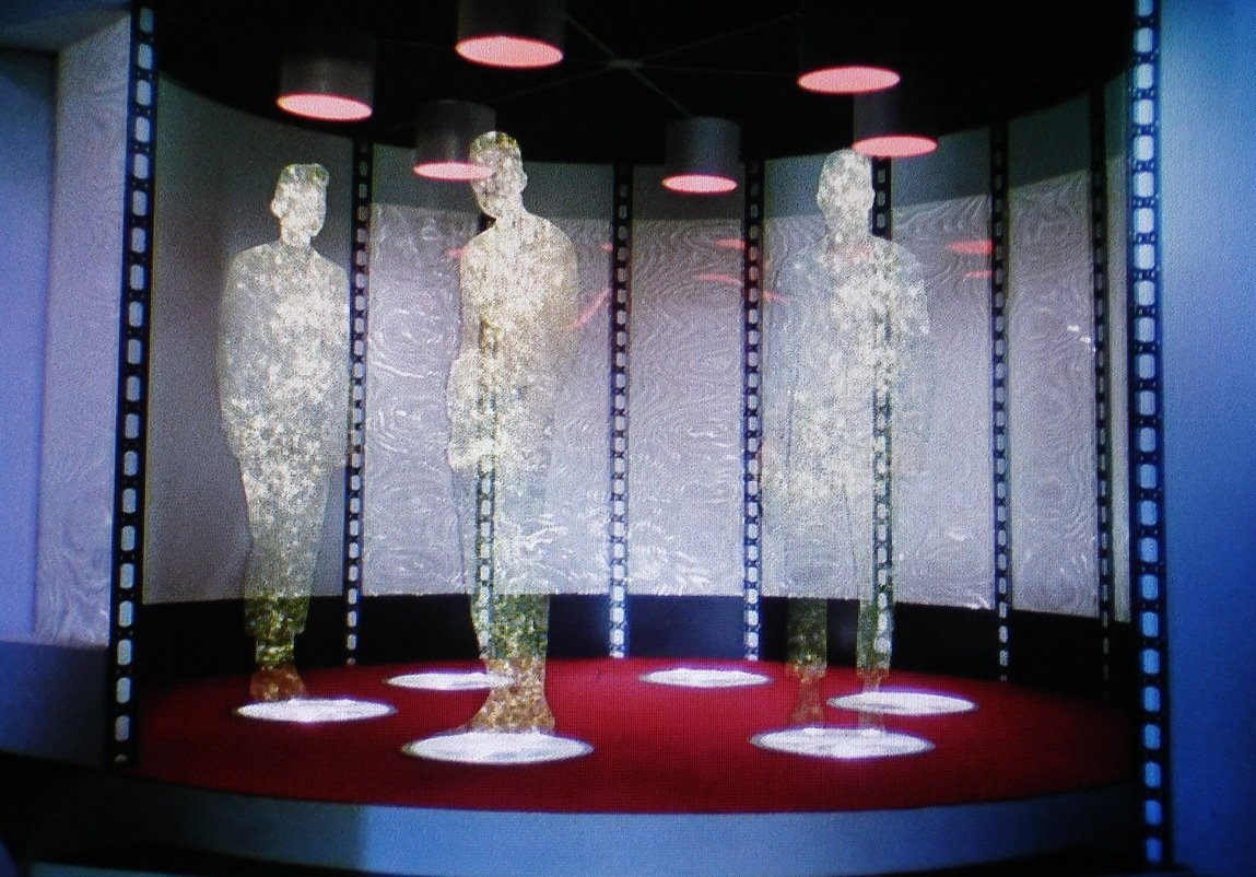 three sparkly people at the Enterprise transporter