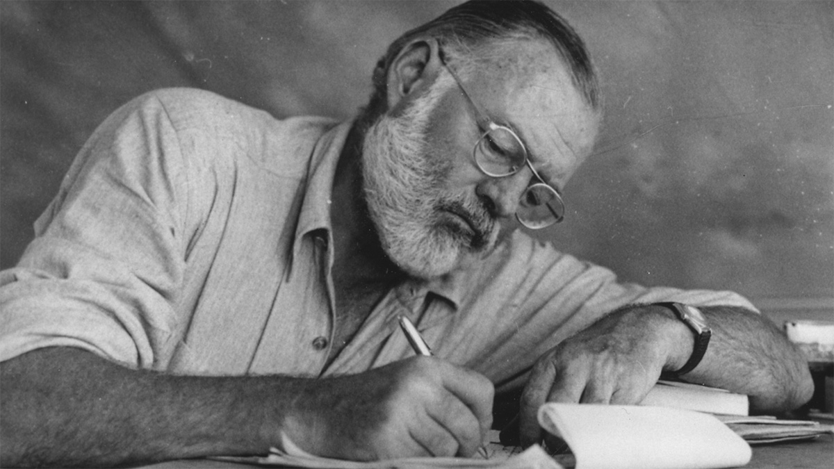 Ernest Hemingway, writing at a table