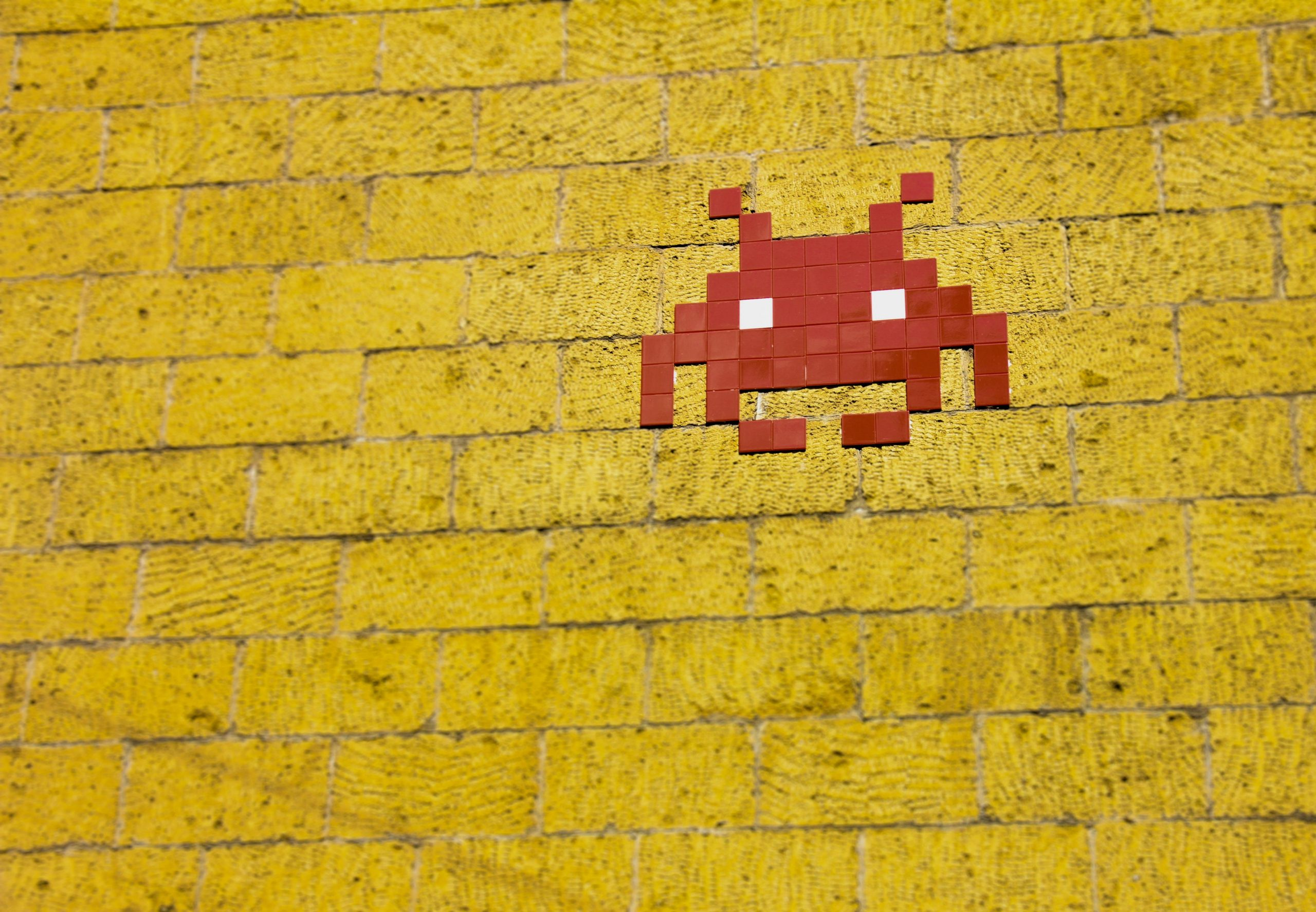 bitmapped red alien on a yellow brick wall