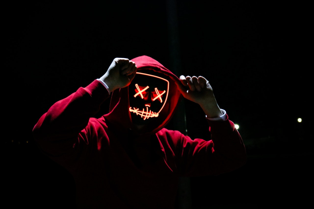 person with neon x'd out facial features under a red hoodie on a black background