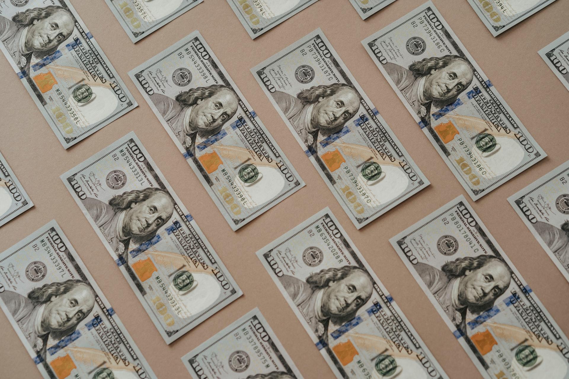 a field of $100 bills on grey