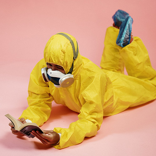 man in hazmat suit reading in a relaxed pose